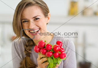 Portrait of smiling young woman with bunch of radishes