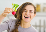 Smiling young woman showing radish