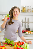 Happy young housewife in modern kitchen showing radish