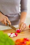 Closeup on woman cutting radishes