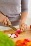 Closeup on woman cutting radishes