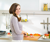 Happy young housewife cutting fresh vegetables in modern kitchen