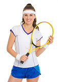 Portrait of smiling female tennis player with racket