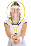 Smiling female tennis player looking through racket