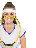 Happy female tennis player holding racket in front of face