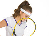 Thoughtful female tennis player holding racket
