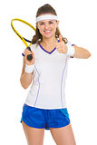 Smiling female tennis player with racket showing thumbs up