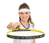 Smiling female tennis player pointing racket in camera