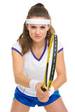 Smiling female tennis player ready to hit ball