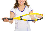 Closeup on smiling female tennis player giving racket
