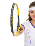 Closeup on female tennis player pointing racket in camera