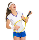 Happy female tennis player playing on racket as on guitar