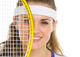 Portrait of female tennis player with racket in front of face