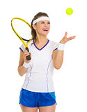 Smiling female tennis player throwing ball up
