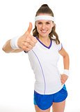 Smiling female tennis player showing thumbs up