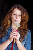 girl blowing on two dandelions