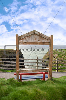 a wooden red bench framed with a sea view