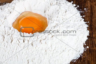 broken egg on flour on wooden table