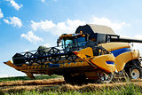 Yellow harvester on field harvesting  wheat