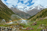 Rainbows in irrigation water spouts in Summer Alps mountain 