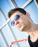 Fashion shot: closeup portrait of handsome young man wearing sunglasses
