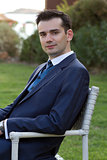 Young man in suit sitting outdoors