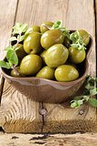 green marinated olives with oregano on a wooden background