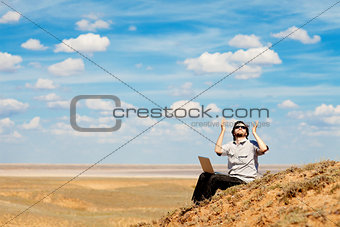 man with laptop praying to the God