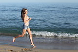 Beautiful casual woman running on the beach