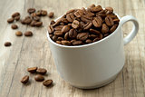 a pile of coffee beans on the wooden background