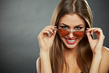 Woman looking over sunglasses and smiling