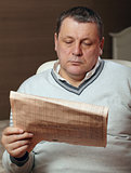Portrait of senior man reading newspaper at home.