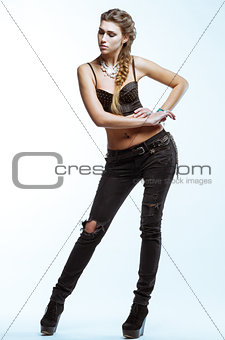 Young blond woman in black top and jeans posing on light backgro