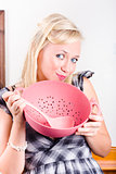 Cute cook holding pink sieve when cooking at home