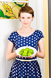 Beautiful girl holding bowl of green limes