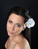 brunette woman with white orchid in hair