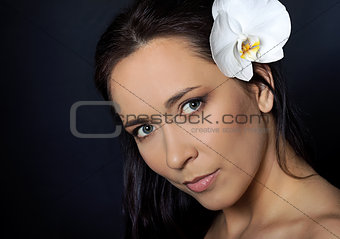 brunette woman with white orchid over black