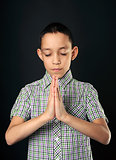 praying boy closed eyes over black
