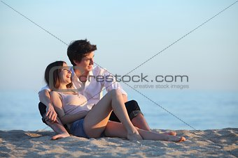 Couple sitting and laughing on the sand of the beach at sunset