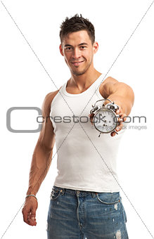 Cropped view of a muscular young man holding clock. It is time for workout concept.