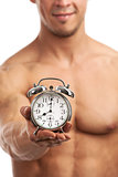 Cropped view of a muscular young man holding clock, It is high time for workout concept.
