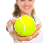 Closeup on ball in hand of happy female tennis player