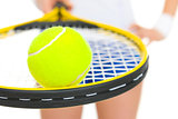 Closeup on female tennis player holding racket with ball