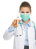 Medical doctor woman in mask showing syringe