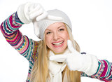 Smiling girl in winter clothes framing with hands