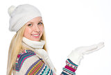 Happy girl in winter clothes presenting something on empty palm