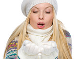 Girl in winter clothes blowing snow