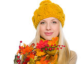 Girl in hat and scarf holding autumn bouquet