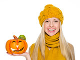 Happy girl in hat and scarf holding jack-o-lantern
