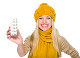 Happy girl in autumn clothes showing pills pack